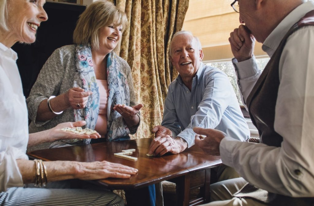 A group of older adults spending time together playing dominoes